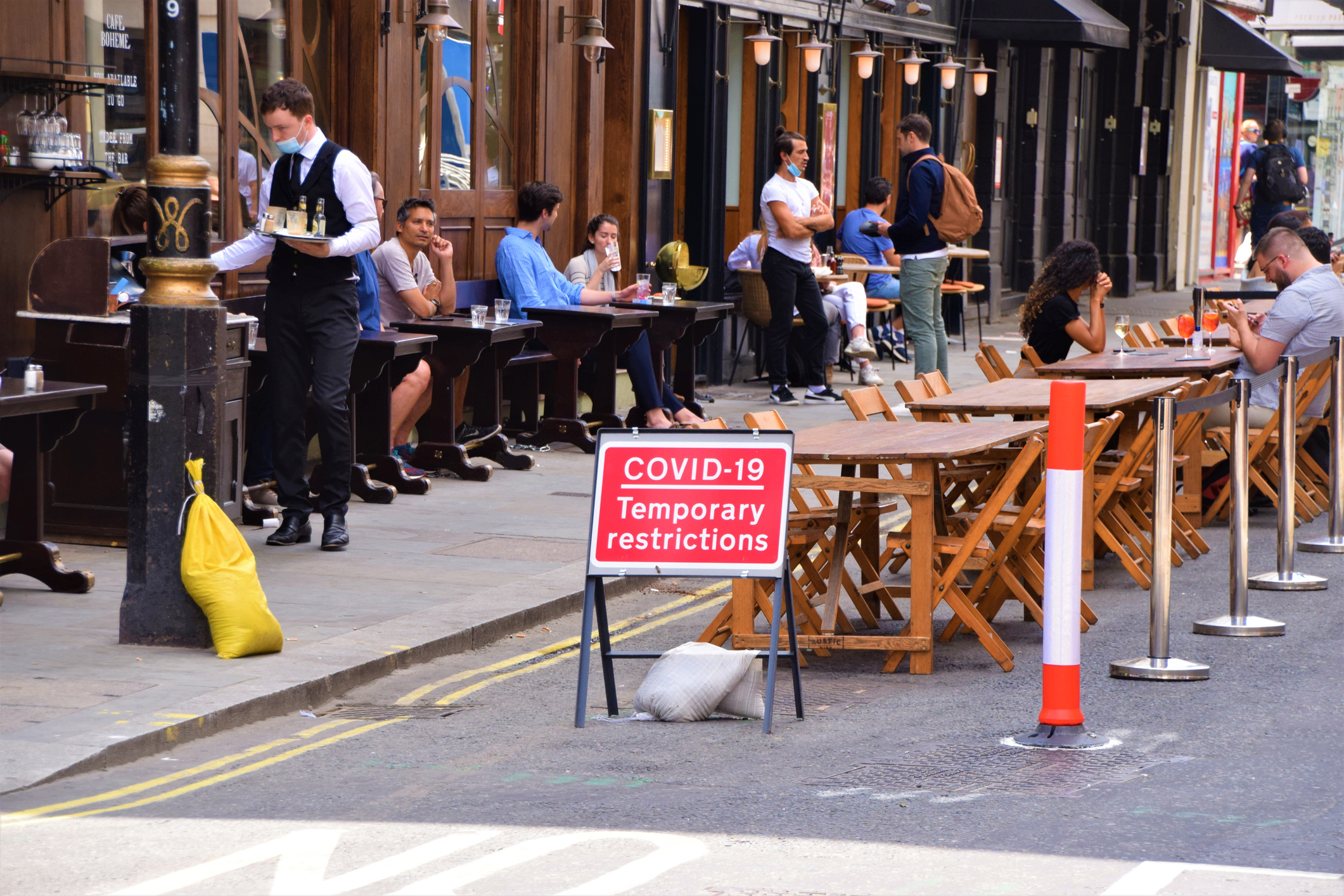 Social distancing outdoor seating with Covid-19 signs, Old Compton Street, Soho, London